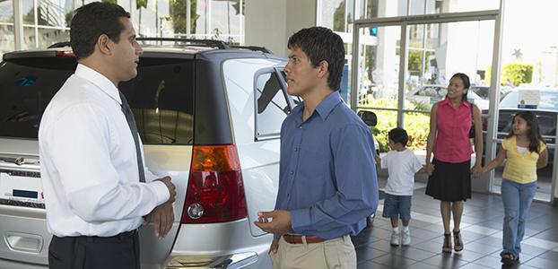 Man shaking car salesman's hand