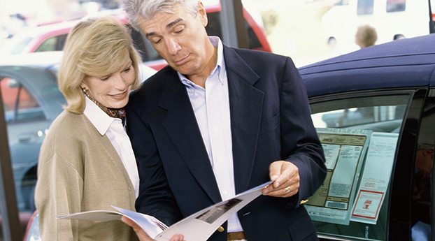 Close-up of a mature couple looking at a brochure